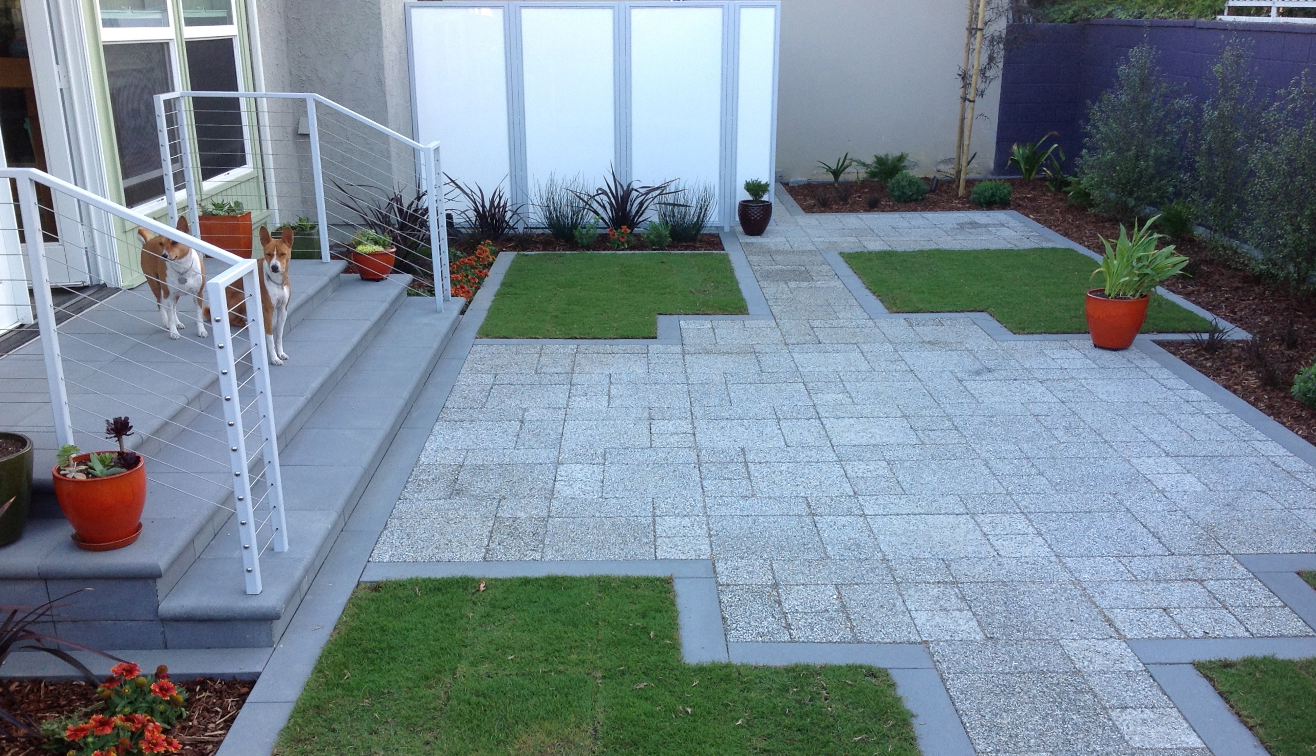 Patio of pervious concrete pavers hugged by 'area rugs' of turf grass